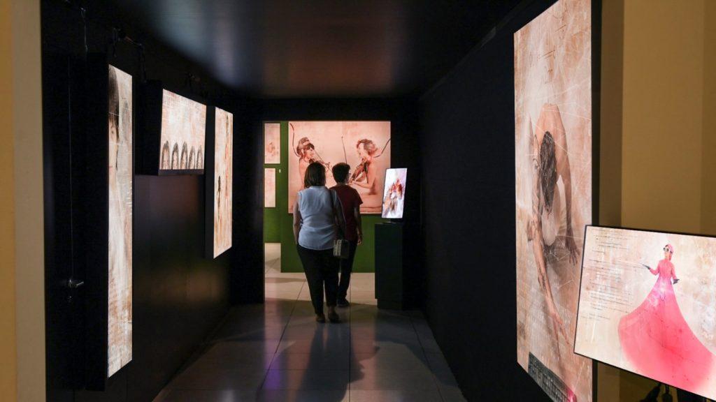 Pasillo con público y obras de la exposición